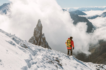 male mountaineer hiking down a steep and snowcovered mountain su