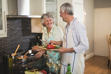 Smiling senior couple preparing food together in kitchen