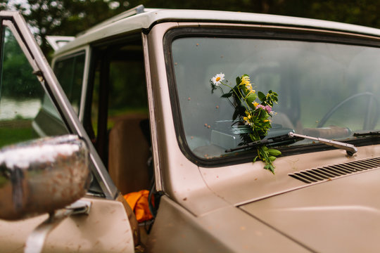 A thoughtful flower bouquet rests on top of a vintage truck