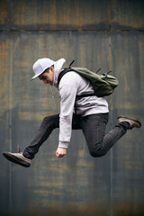 Young man jumping in front of an urban wall