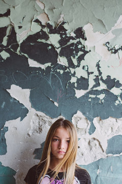 Portrait of young girl standing next to an old wall