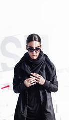 Portrait of attractive alterantive female in black urban outfit on white abstract background