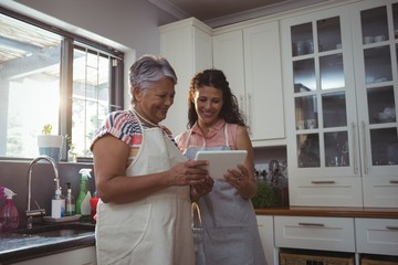 Mother and daughter using digital tablet in kitchen