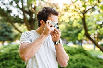 Handsome man in park taking photos with analog camera
