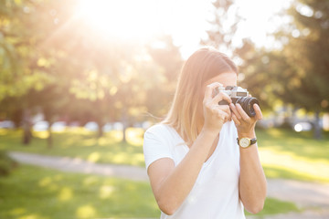 Cute girl on sunny day in parking taking photos with analog camera