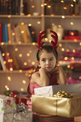 Sad little girl sitting in front of presents