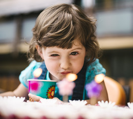 Little girl blowing on the birthday candles