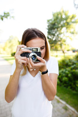 Young girl in park using her free time to take photographs