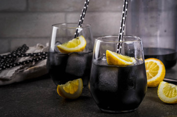 Trendy food. Summer refreshment drinks. Detox and diet concept. Black lemonade with charcoal, ice, lemon juice and lemon. On a home stone table, with black straws for drinking. Copy space