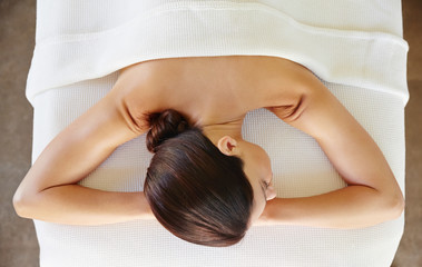 Overhead view of relaxed young woman lying on massage table