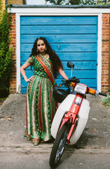 Beautiful Indian woman wearing a sari and with a moped