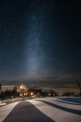 alpine cabin in snowy mountain landscape at night with the milky way above
