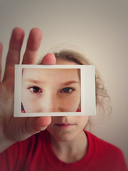 Girl Holding Up Printed Image Of Eyes