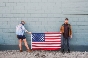 Young gay couple holding an American flag