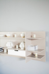 Shelf with white ceramic cups on gray wall