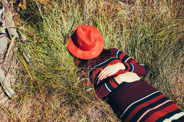 Anonymous woman hiding her face with a hat lying on the grass