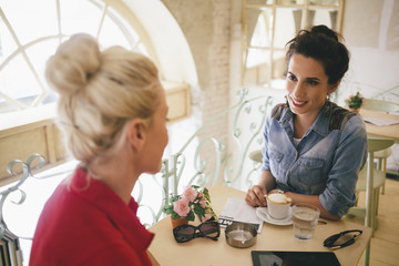 Two Smiling Caucasian Women Chatting at a Cafe