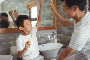 Father and son giving high five to each other in bathroom