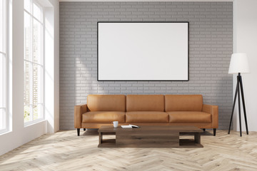 Gray living room with a beige sofa, poster, lamp