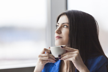 Close up of pensive businesswoman with coffee cup