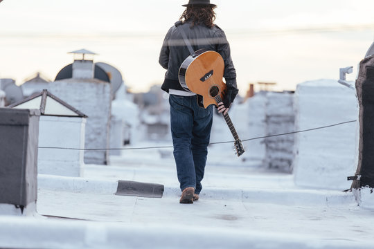 Young musician has guitar on rooftop