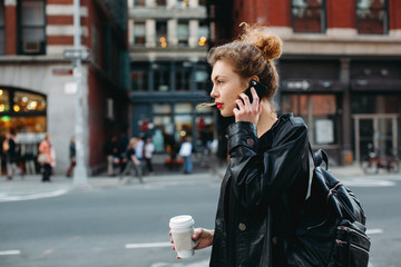 Business woman walking down the street holding up her cell phone and her coffee mug