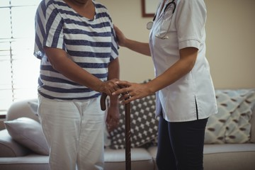 Female doctor helping senior woman to walk with walking stick