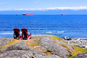 Red wooden chairs overlooking the Pacific Ocean near Victoria, BC, Canada