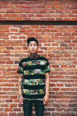 Portrait of a young tattooed man standing in front of a brick wall