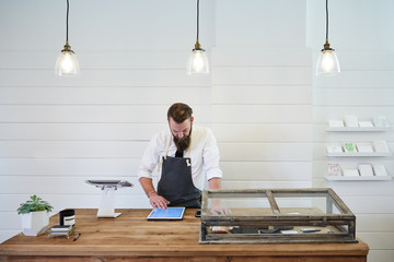 Small business owner working on digital tablet in artisan retail shop