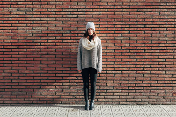 Portrait of girl with winter clothes on brick wall