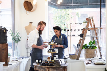 Millennial co-workers talking and working together in small retail shop