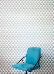 Blue office chair against pattern wallpaper