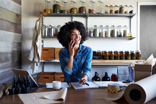 Millennial African American Woman businesswoman on the phone in her skincare studio