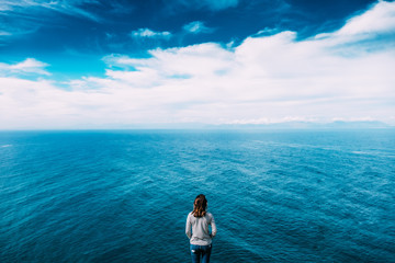 Woman overlook an expansive sea view from above