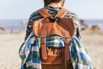 Traveler woman with leather backpack outdoors