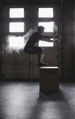 Young, fit man doing box jumps in gym