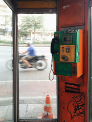 payphone booth with biker riding in background thailand