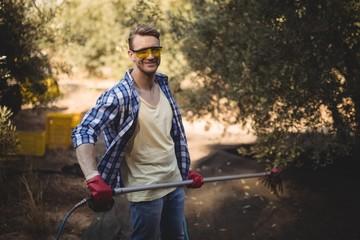 Smiling man holding rake at olive farm