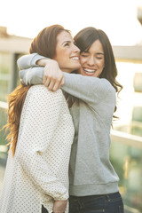 Happy young girlfriends hugging together on the city