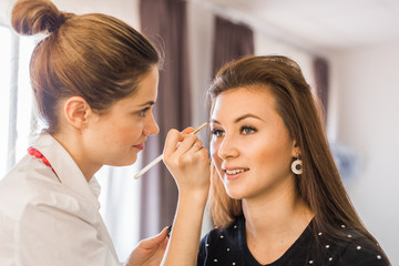 beauty and makeup concept - closeup portrait of beautiful woman getting professional make-up with brush
