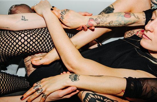 Three tattooed women holding hands