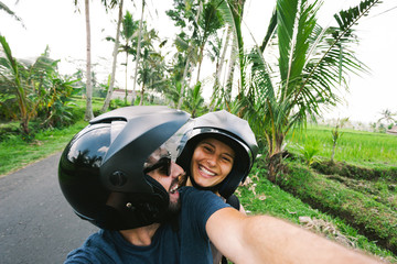 Couple taking a selfie on a motorcycle in the roads of Bali