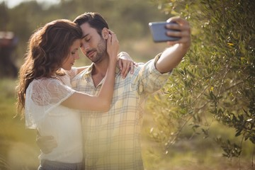 Romantic couple taking selfie by tree