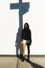 Young woman standing in the pole shadow in the street