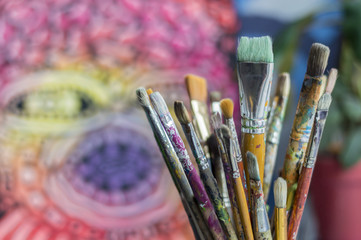 diferent brushes in multicolored paint closeup a