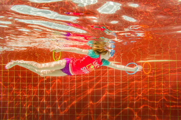 Little Girl Swimming After Rings Underwater In All Inclusive Luxury Resort Pool on Caribbean Vacation