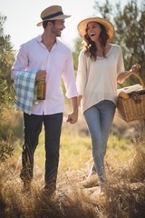 Cheerful young couple carrying picnic basket