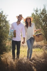 Foto auf Acrylglas Picknick Portrait of happy young couple carrying picnic basket