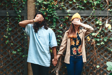 Young hipster couple hiding their faces on ivy background